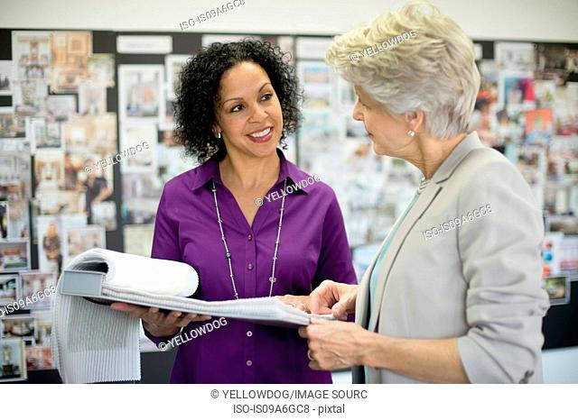 Two textile designers discussing notebook