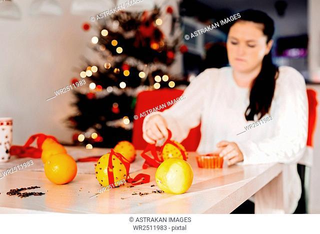 Woman preparing Christmas decorations at table