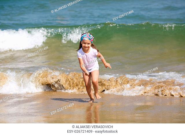 Child runs along the beach on a background of a sea wave. Shallow depth of field. Focus on model