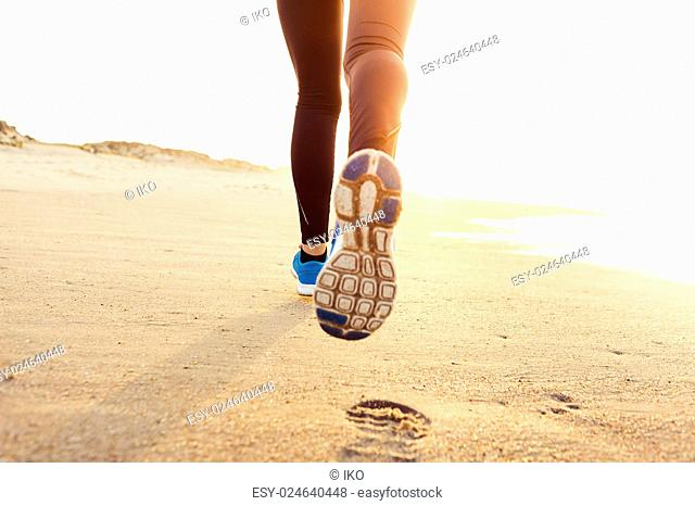 Beautiful and healthy woman running on the beach