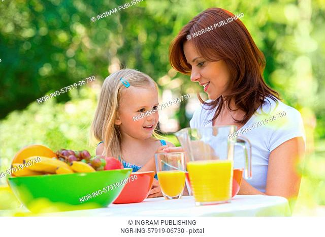 Mother and daughter picnicking at park or backyard