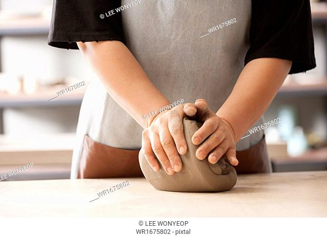 a woman working on a clay ball