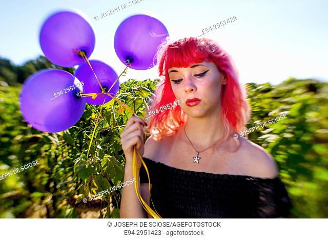 A 25 year old woman with pink hair, looking down in a field of sunflowers holding balloons, Alabama USA