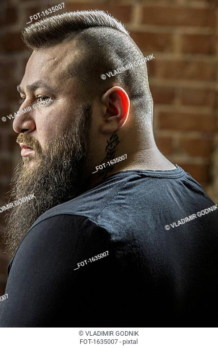 Close-up of male hairdresser with beard looking away at barber shop