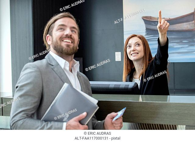 Female receptionist showing room to businessman
