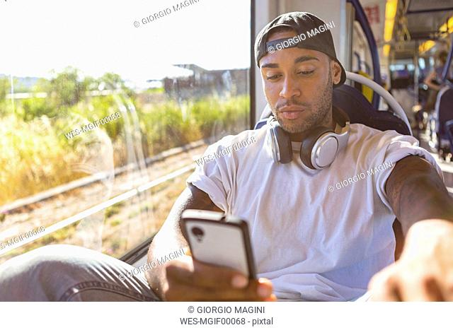 Portrait of young man in tramway looking at smartphone