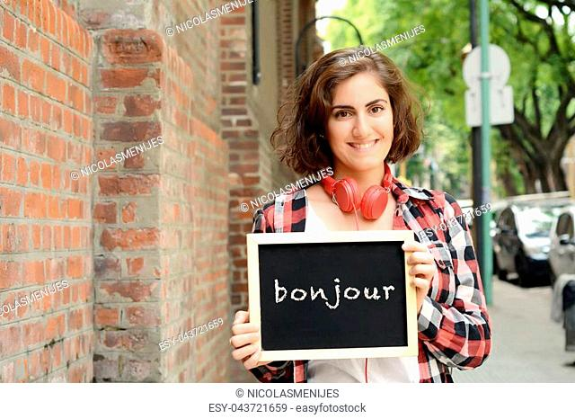 "Young beautiful woman holding chalkboard with text """"Bonjour"""". Outdoors"