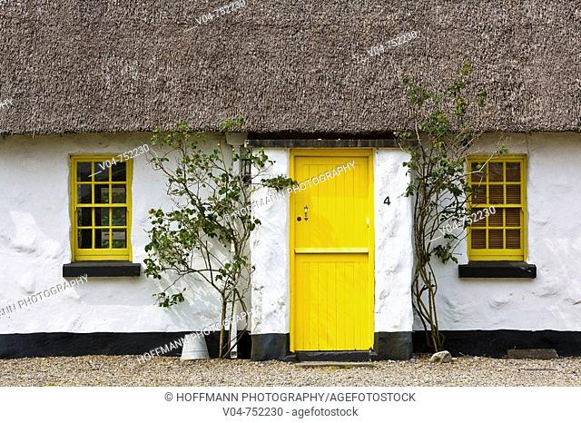 Picturesque thatched cottage with yellow door and windows in Ballyvaughan, Ireland, Europe