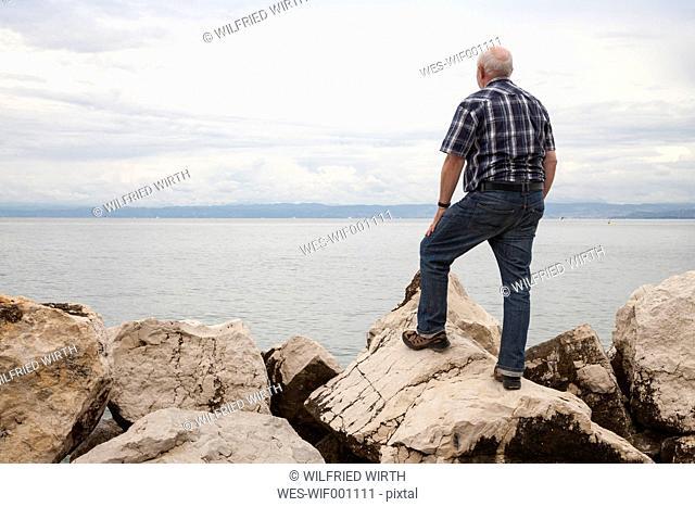 Slovenia, Piran, man standing on rocks at waterside looking at horizon