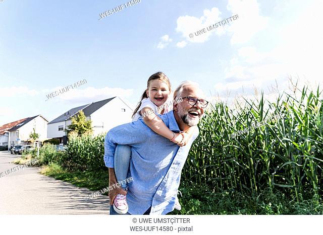 Grandfather carrying granddaughter piggyback