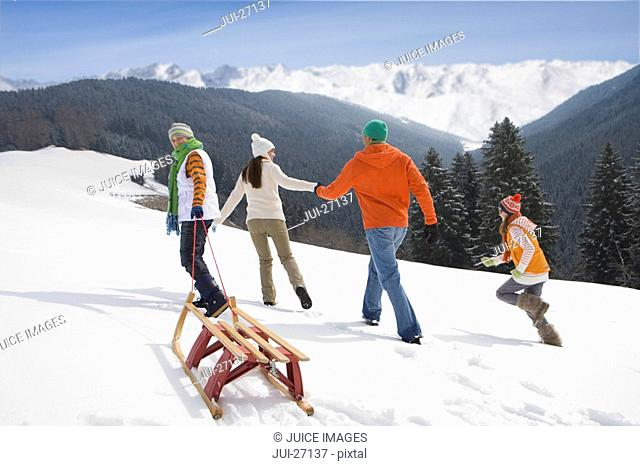 Family pulling sled up mountain top ski slope