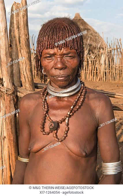 Elderly Hamar woman with red clay in her hair and with necklaces, Omo river valley, Southern Ethiopia