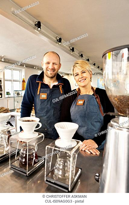 Portrait of mature couple in coffee shop kitchen
