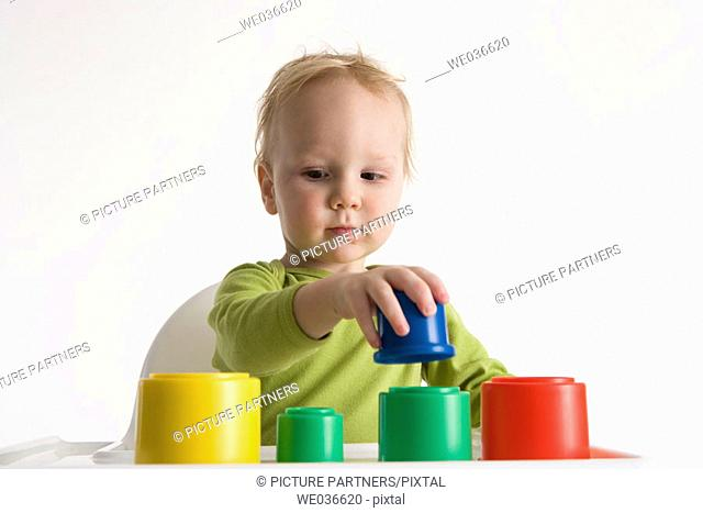 Toddler playing with coloured cups