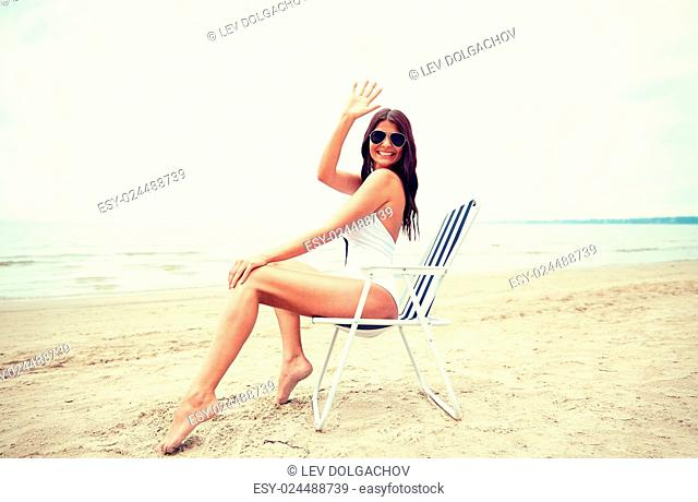 summer vacation, tourism, travel, holidays and people concept - smiling young woman sunbathing in lounge or folding chair pointing finger on beach