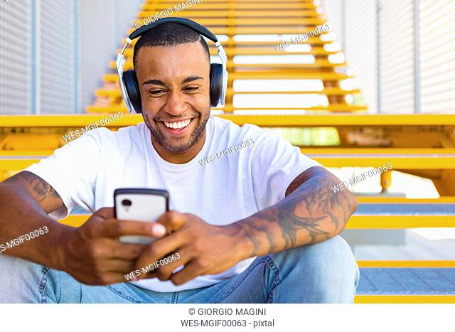 Portrait of laughing young man with headphones sitting on stairs looking at smartphone