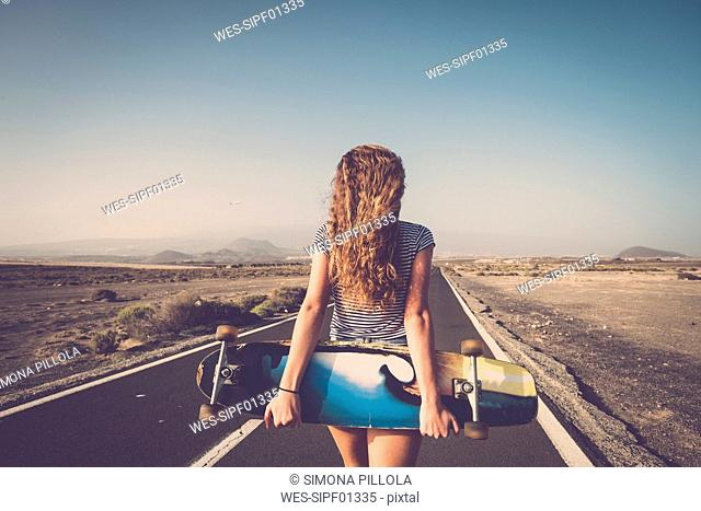 Spain, Tenerife, back view of blond young woman with longboard standing on empty country road
