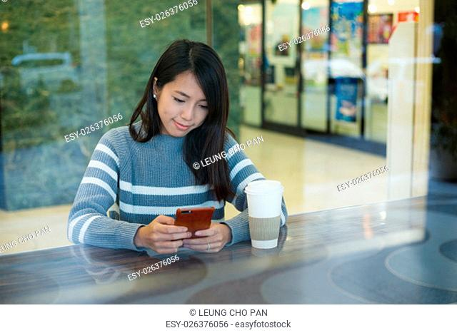 Woman look at cellphone in cafe