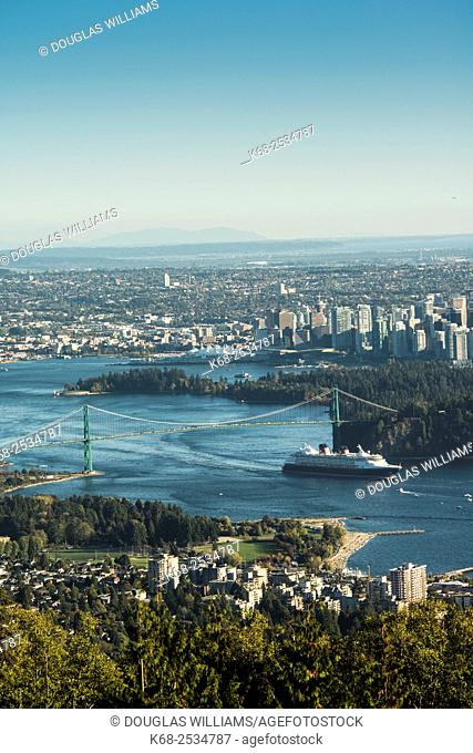 A cruise ship passes under the Lions Gate Bridge as it leaves port in Vancouver, BC, Canada