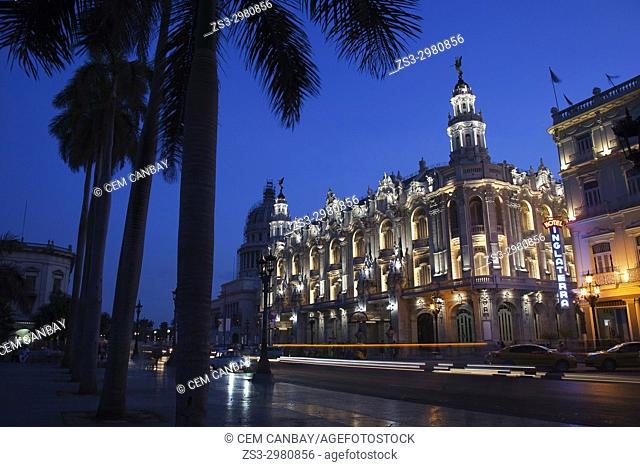 View to the Gran Teatro-Grand Theatre building and Hotel Inglaterra with silhouette of palm trees in the foreground in Central Havana by night, La Habana, Cuba