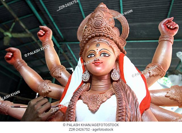 A Bangladeshi idol-maker puts the finishing touches to a clay statue of the Hindu goddess Durga in a Temple in Dhaka on October 4, 2013