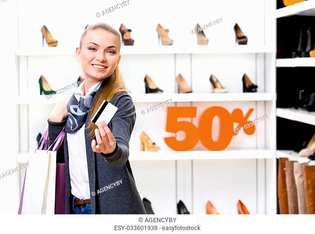 Woman showing credit card in footwear shop with great variety of stylish shoes and 50% sale