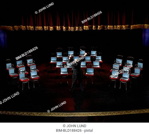 Hispanic male conductor in front of laptops on chairs