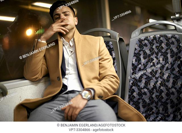 young man sitting in bus at night, in Berlin, Germany