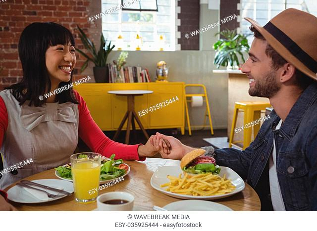 Couple holding hands at cafe