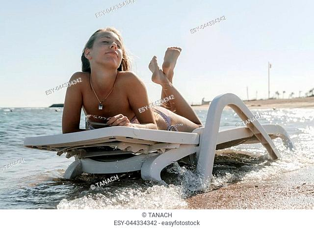 Young woman in chaise lounge at the sea beach. Girl relax on beach