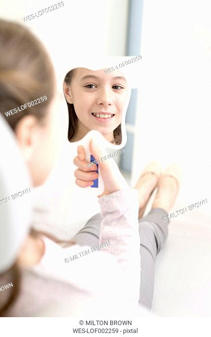 Smiling girl at the dentist looking in hand mirror