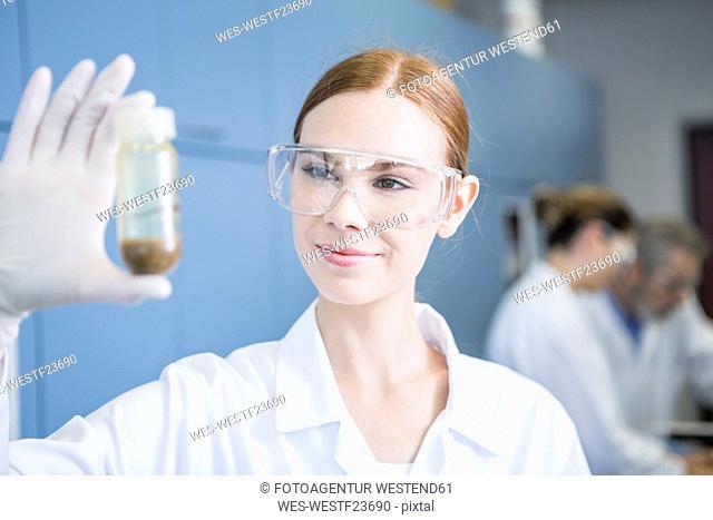 Smiling scientist in lab examining sample