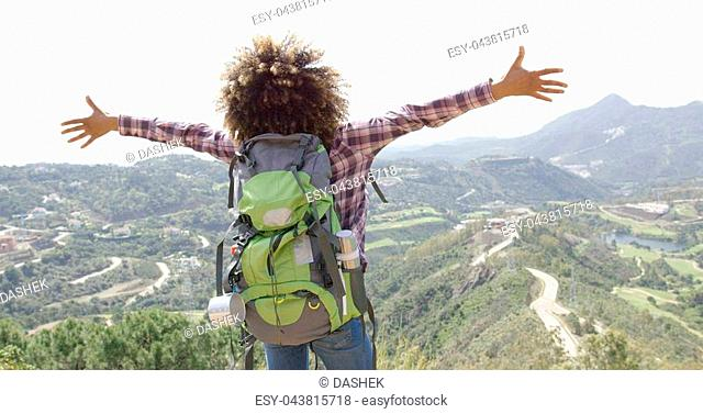 Back view of young happy woman with backpack standing with hands apart and enjoying mountains in summer