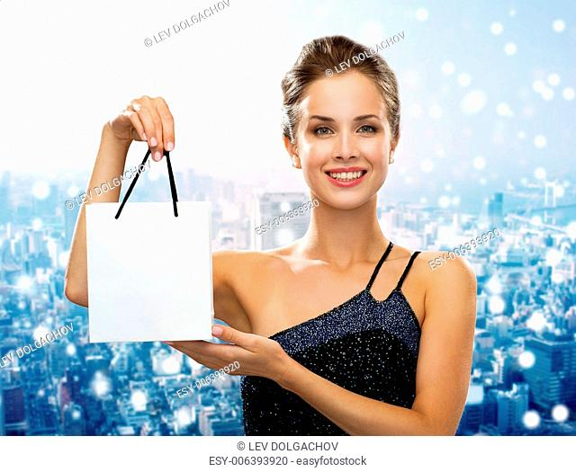 christmas, sale, advertisement, holydays and people concept - smiling woman with white blank shopping bag over snowy city background