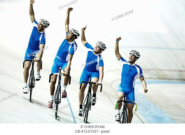 Track cycling team riding in velodrome with arms raised