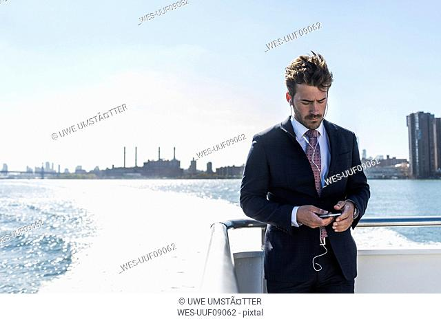 USA, New York City, businessman on ferry on East River with cell phone and earphones