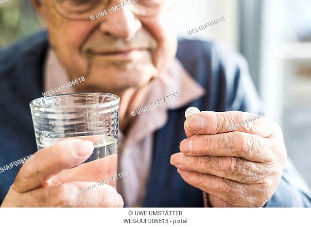 Hands of senior man holding tablet and glass of water, close up