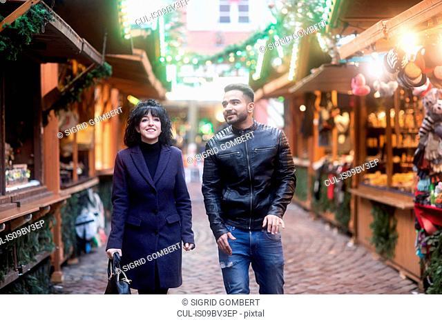 Couple window shopping at Christmas market, Freiburg, Baden-Wurttemberg, Germany