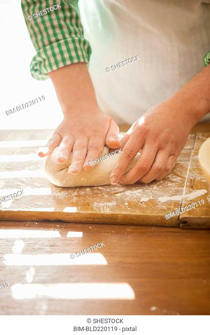 Close up of baker shaping dough on counter