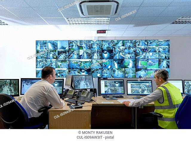 Security guards in security control room with video wall