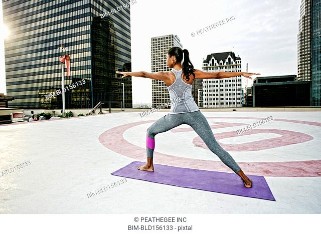 African American woman practicing yoga on urban rooftop