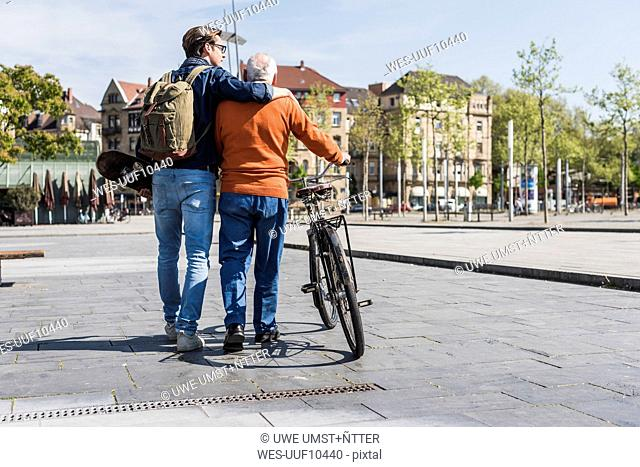 Senior man with bicycle and adult grandson in the city on the move