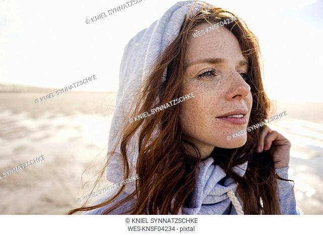 Woman wearing hood on a windy beach