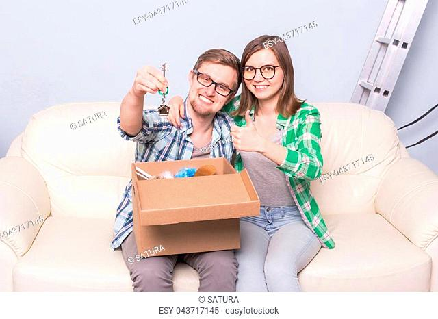 Home, people and gesture concept - young man holding the keys and woman showing thumb up