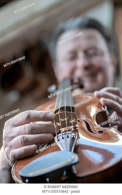 Craftsman hands examining violin at workshop