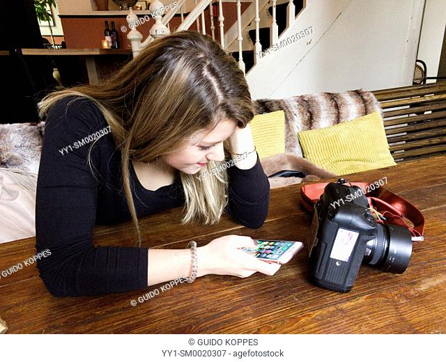 Tilburg, Netherlands. Young adult, caucasian woman playing with her smartphone and a photo camera while visiting a cafe and restaurant