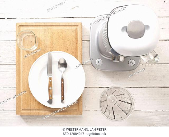 Kitchen utensils: a blender, measuring cup, cutlery and a plate