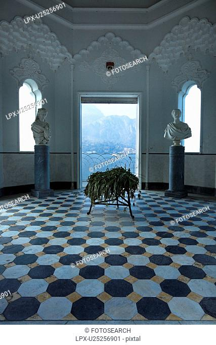 Interior of Tempio at Villa Melzi with ornate stucco interior, black and white geometric pattern of floor, arched windows and doorway with view onto Lake Como