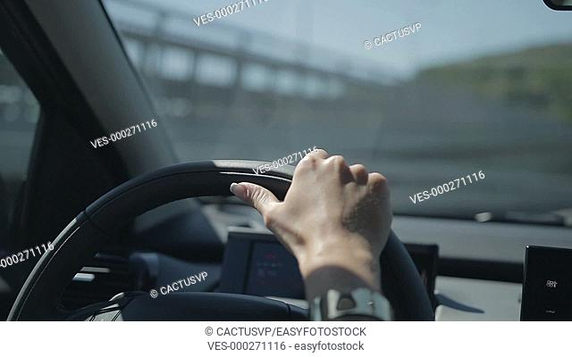Young woman driving car and making a turn
