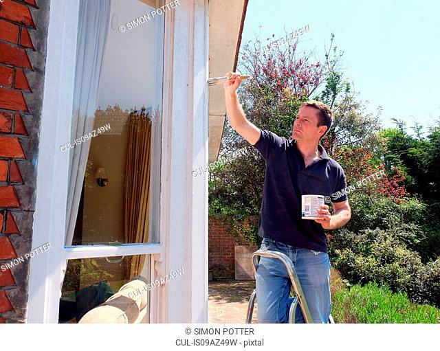 Man on ladder painting window frame